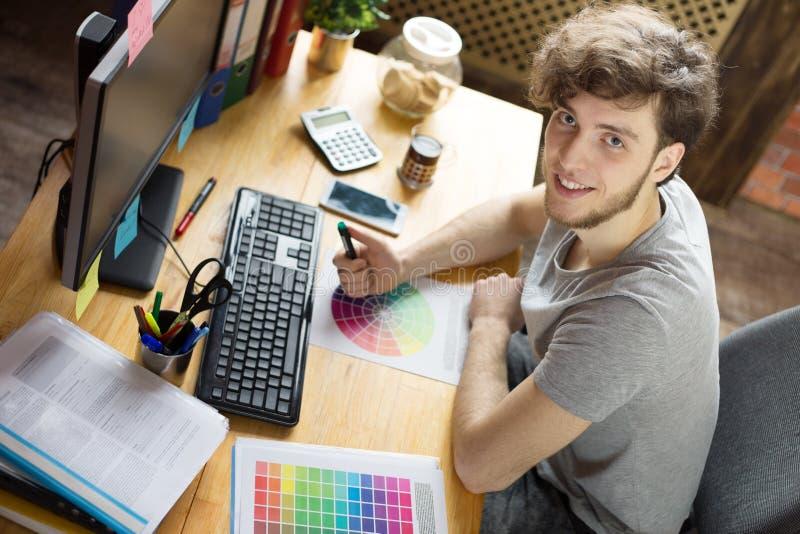 Hombre sonriente joven que trabaja en su lugar de trabajo fotografía de archivo