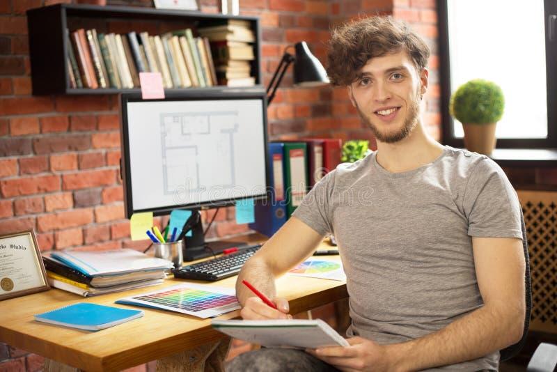 Hombre sonriente joven que trabaja en su lugar de trabajo fotografía de archivo libre de regalías