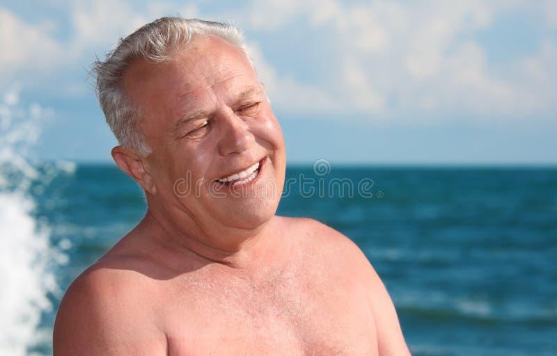 Hombre sonriente mayor en la costa imagenes de archivo