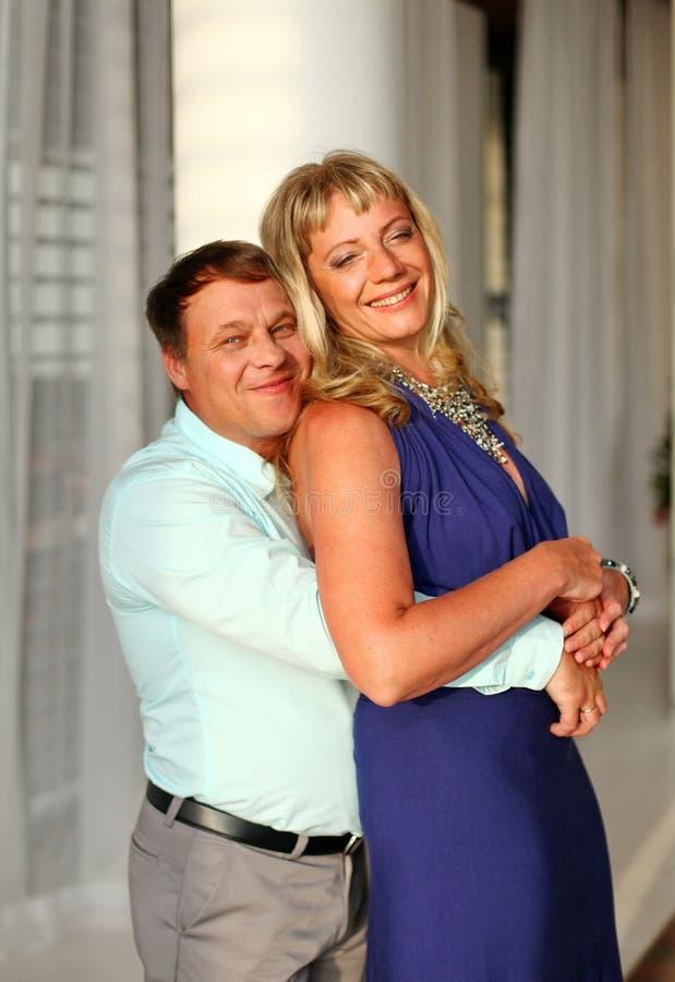 Hombre sonriente que abraza a una mujer alta foto de archivo libre de regalías