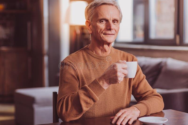 Hombre sonriente que come té una relajación fotos de archivo libres de regalías