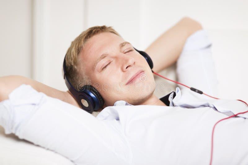 Hombre sonriente que disfruta de música que escucha en los auriculares con clo de los ojos fotos de archivo libres de regalías