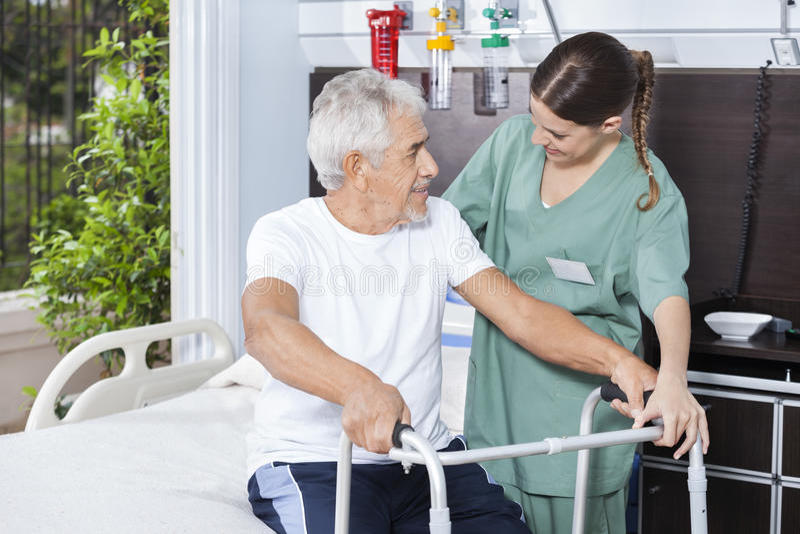 Hombre sonriente que es ayudado por el marco de In Using Zimmer de la enfermera imagenes de archivo