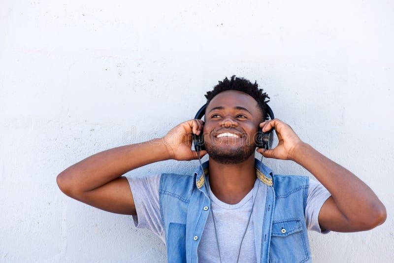 Hombre sonriente que escucha la música con las manos los auriculares foto de archivo