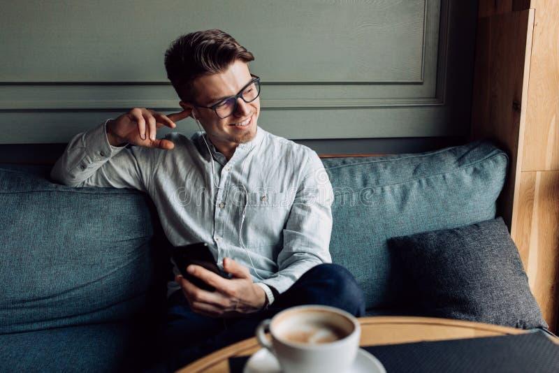 Hombre sonriente que escucha la música en auriculares mientras que teniendo rotura-tiempo en el café fotos de archivo