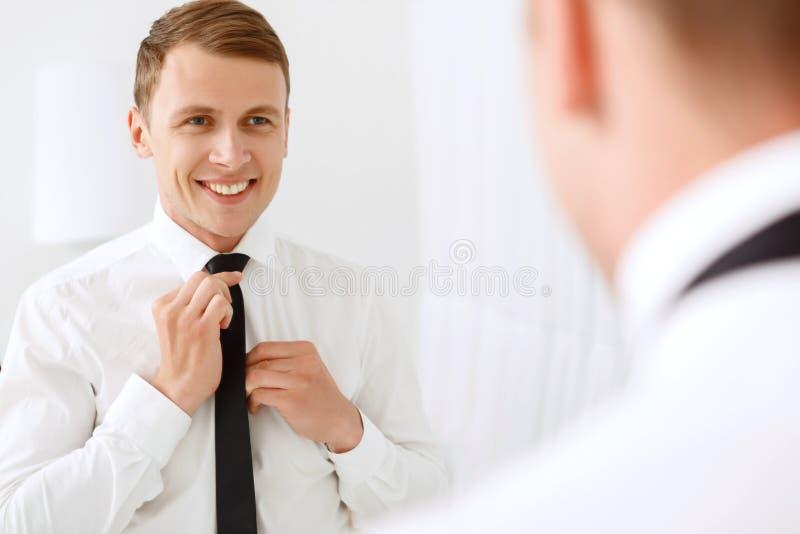 Hombre sonriente que fija su lazo fotos de archivo