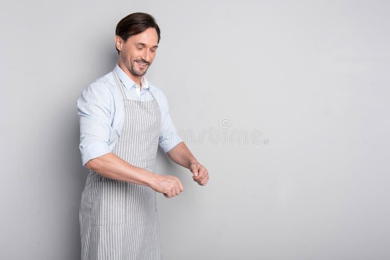 Hombre sonriente que gesticula en un delantal en un fondo gris foto de archivo