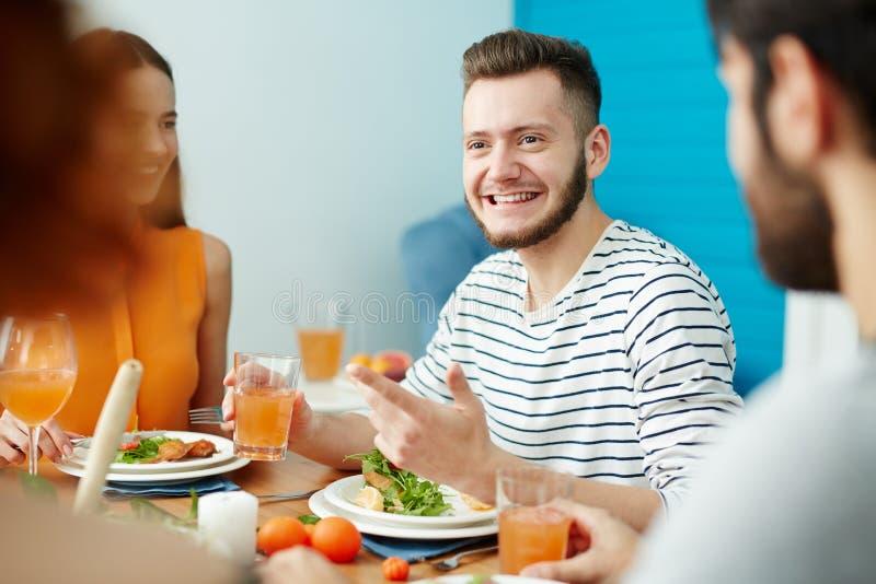 Hombre sonriente que habla con los amigos mientras que come junto fotos de archivo libres de regalías
