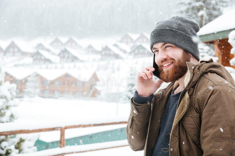 Hombre sonriente que habla en el teléfono celular al aire libre en tiempo nevoso fotos de archivo