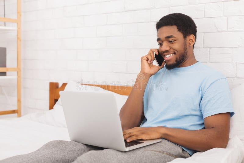 Hombre sonriente que habla en el teléfono y usar el ordenador portátil en cama imagen de archivo libre de regalías