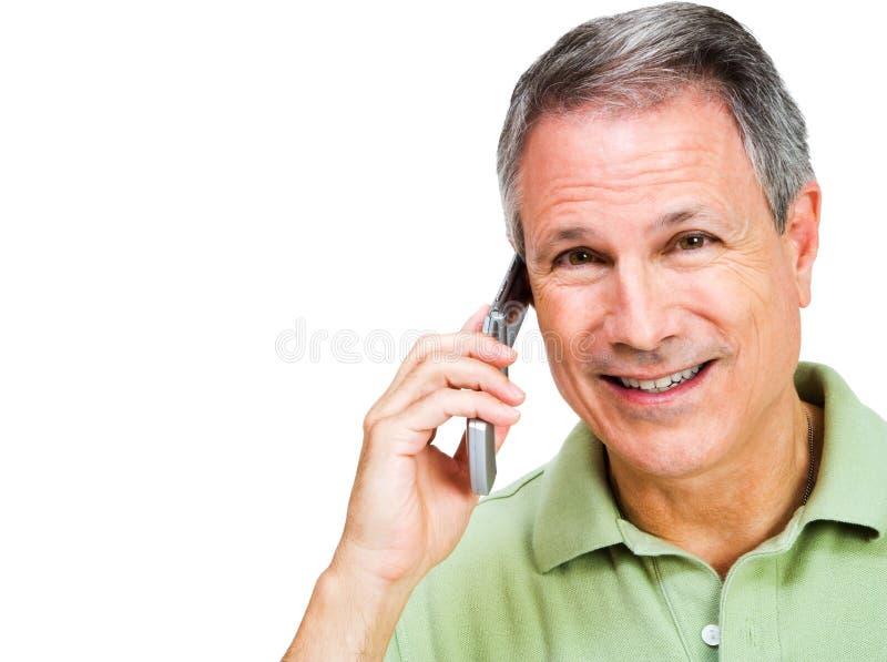 Hombre sonriente que habla en móvil foto de archivo