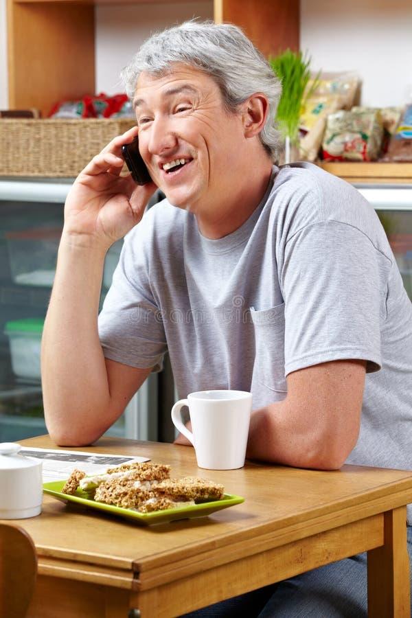 Hombre sonriente que hace llamada en café fotos de archivo
