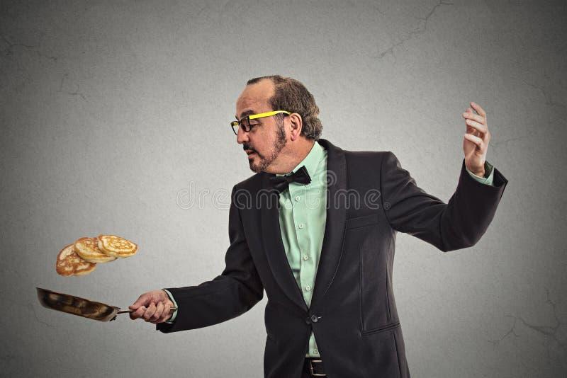Hombre sonriente que lanza las crepes en el sartén fotografía de archivo