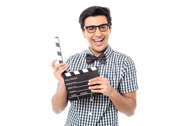Hombre sonriente que lleva a cabo una palmada de la película fotos de archivo