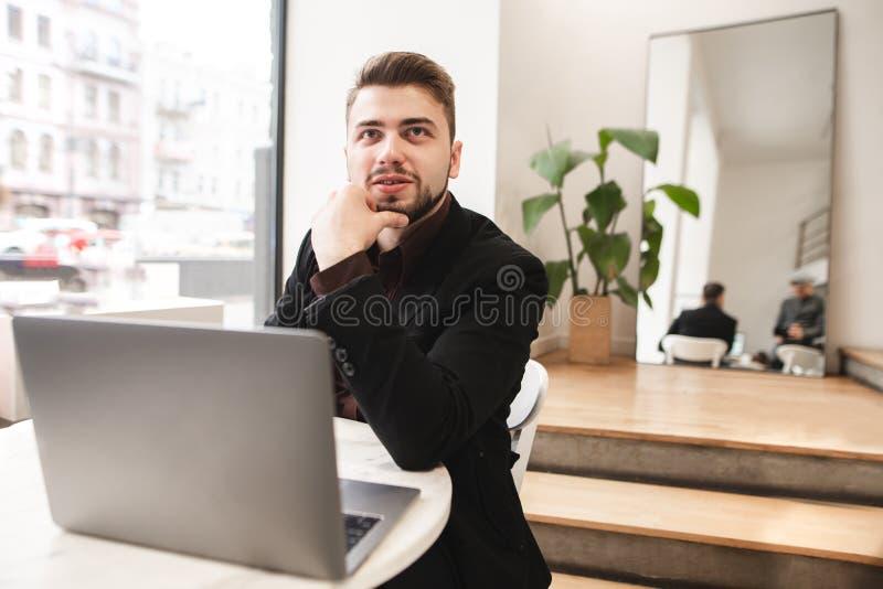 Hombre sonriente que lleva un traje y una barba que se sientan con un ordenador portátil en una tabla en un restaurante acogedor fotos de archivo