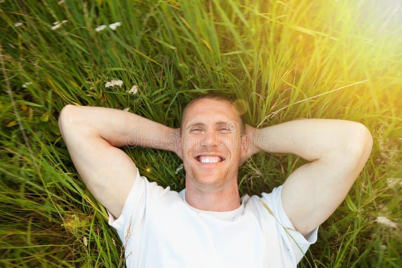 Hombre sonriente que miente en hierba imagenes de archivo