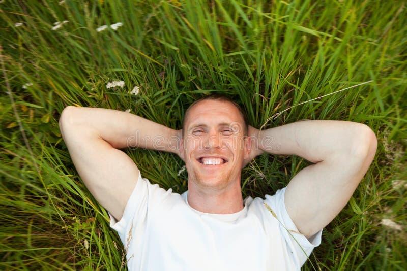 Hombre sonriente que miente en hierba fotos de archivo