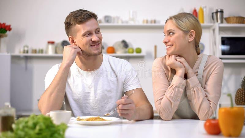 Hombre sonriente que mira con amor la esposa, agradecida para la cena sabrosa, matrimonio feliz imagenes de archivo