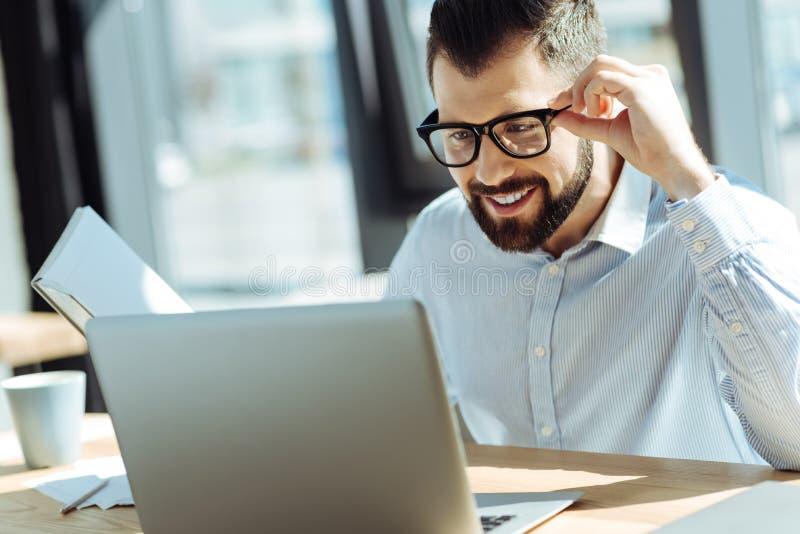 Hombre sonriente que mira el ordenador portátil mientras que sostiene el cuaderno foto de archivo