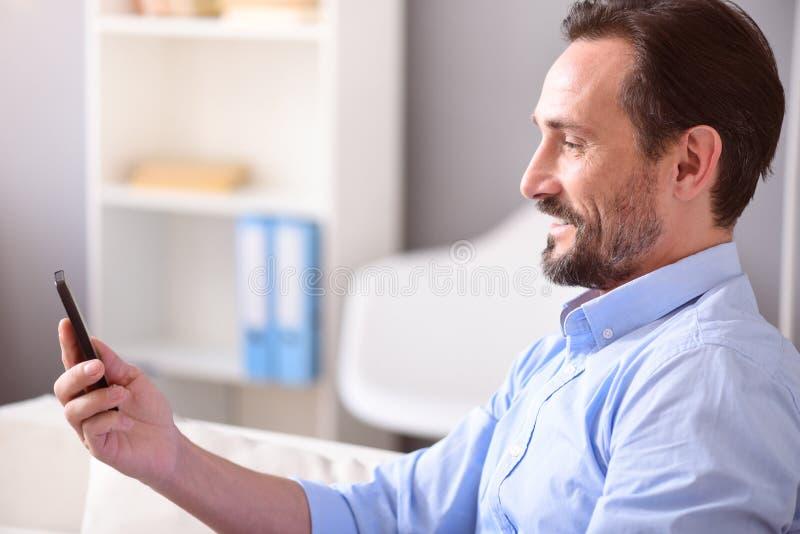 Hombre sonriente que mira su teléfono foto de archivo libre de regalías