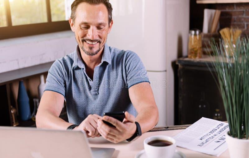 Hombre sonriente que mira su teléfono imagenes de archivo