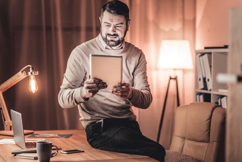 Hombre sonriente que mira un vídeo en una tableta fotos de archivo