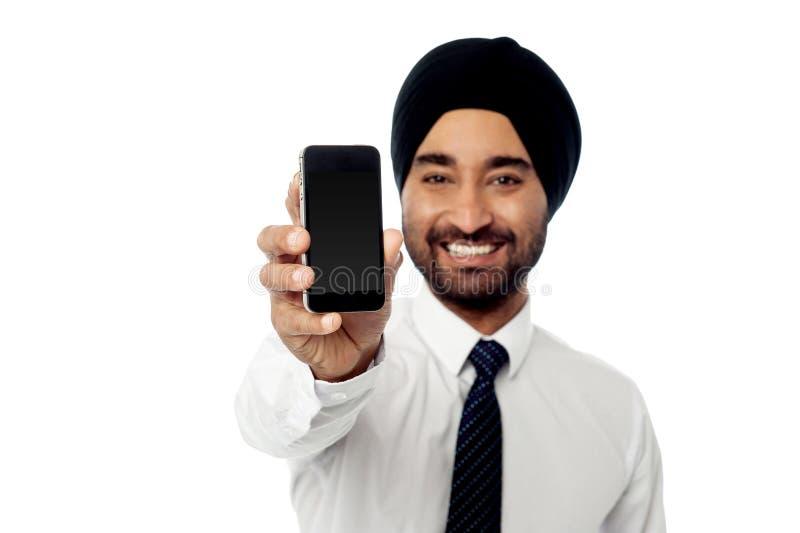 Hombre sonriente que muestra su nuevo teléfono móvil imagen de archivo libre de regalías