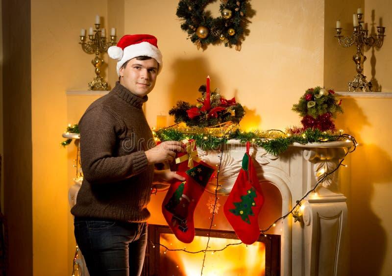 Hombre sonriente que presenta con la caja de regalo en la chimenea adornada imágenes de archivo libres de regalías