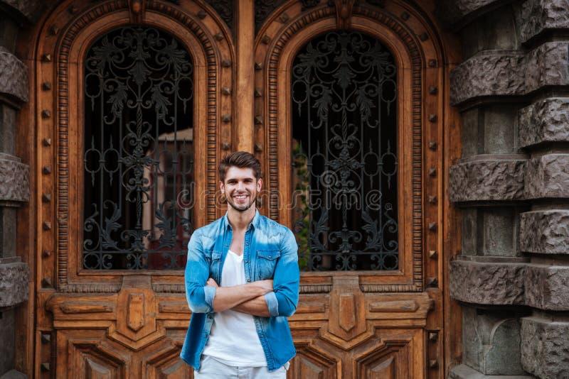 Hombre sonriente que se coloca delante de la puerta de madera hermosa fotografía de archivo libre de regalías