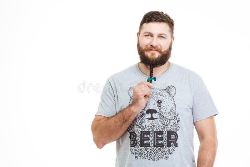 Hombre sonriente que se coloca y pequeña trenza conmovedora en su barba imagen de archivo libre de regalías