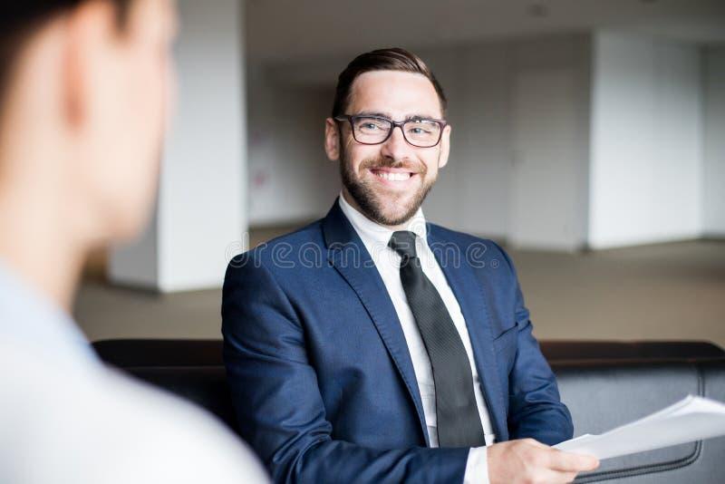 Hombre sonriente que sienta y que mira a la persona fotos de archivo