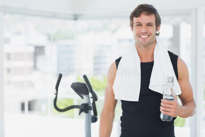 Hombre sonriente que sostiene la botella de agua en la clase de giro en gimnasio brillante fotos de archivo