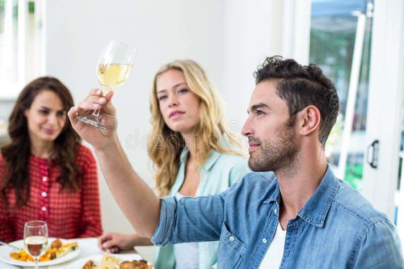 Hombre sonriente que sostiene la copa de vino blanca con los amigos imagen de archivo libre de regalías