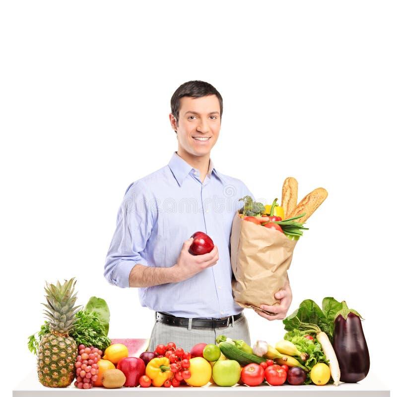 Hombre sonriente que sostiene una manzana y un bolso con los productos alimenticios imágenes de archivo libres de regalías