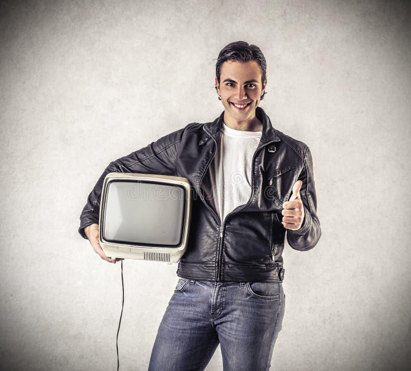Hombre sonriente que sostiene una televisión del vintage foto de archivo libre de regalías