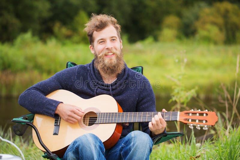 Hombre sonriente que toca la guitarra en acampar imagen de archivo libre de regalías