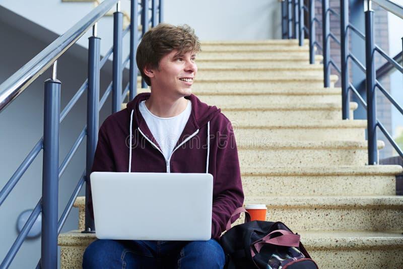 Hombre sonriente que trabaja en ordenador portátil mientras que mira hacia fuera la ventana imagen de archivo libre de regalías