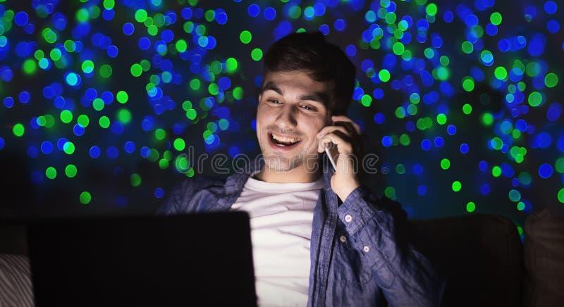 Hombre sonriente que trabaja tarde en casa en el ordenador portátil fotografía de archivo libre de regalías