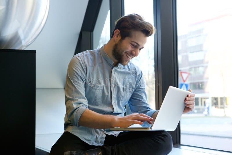 Hombre sonriente que usa la computadora portátil imágenes de archivo libres de regalías