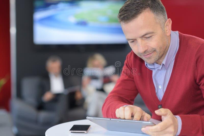 Hombre sonriente que usa la tableta foto de archivo libre de regalías
