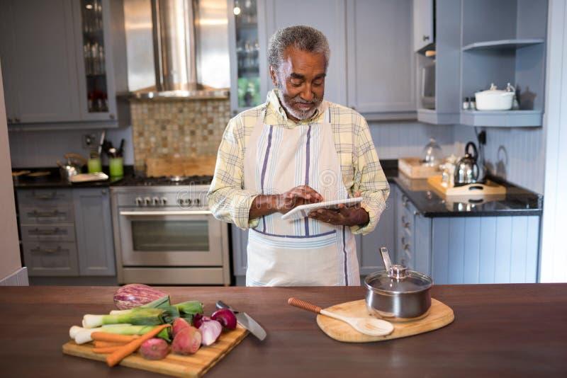 Hombre sonriente que usa la tableta mientras que cocina la comida imagen de archivo