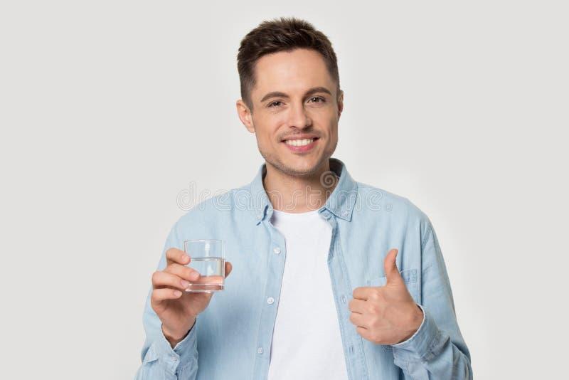 Hombre sonriente sano que sostiene el vaso de agua que muestra los pulgares para arriba fotos de archivo