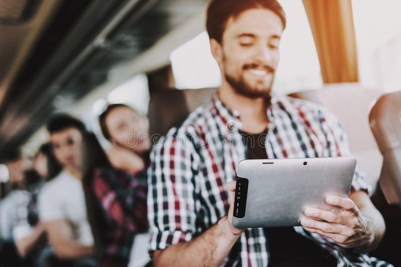 Hombre sonriente usando la tableta de Digitaces en autobús turístico fotos de archivo