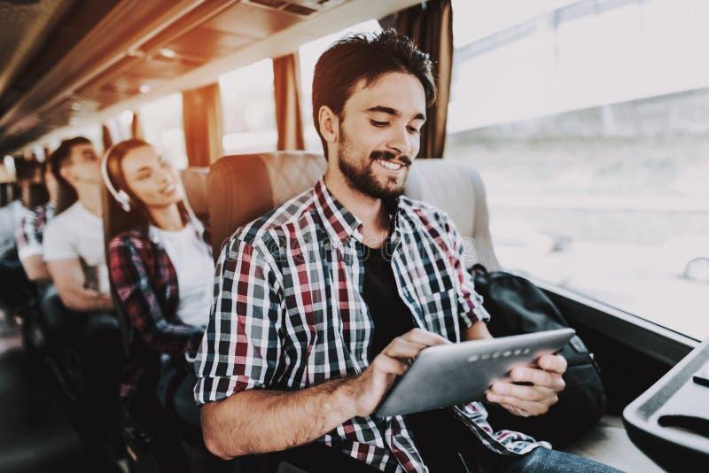 Hombre sonriente usando la tableta de Digitaces en autobús turístico foto de archivo libre de regalías