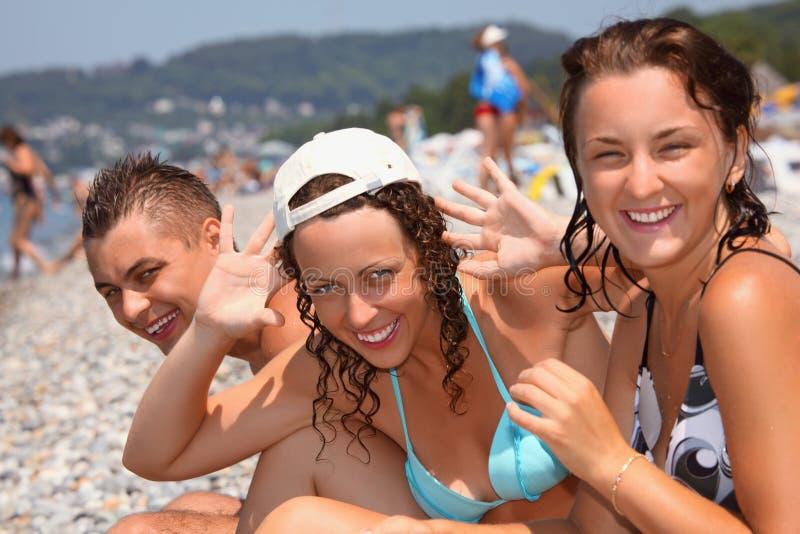Hombre sonriente y dos mujeres jovenes en la playa pedregosa fotos de archivo libres de regalías