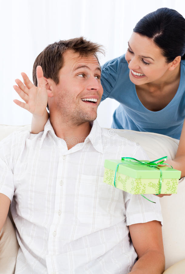 Hombre sorprendente que recibe un presente de su novia foto de archivo