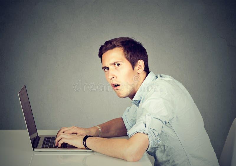 Hombre sorprendido con el ordenador portátil que se sienta en el escritorio imagen de archivo libre de regalías