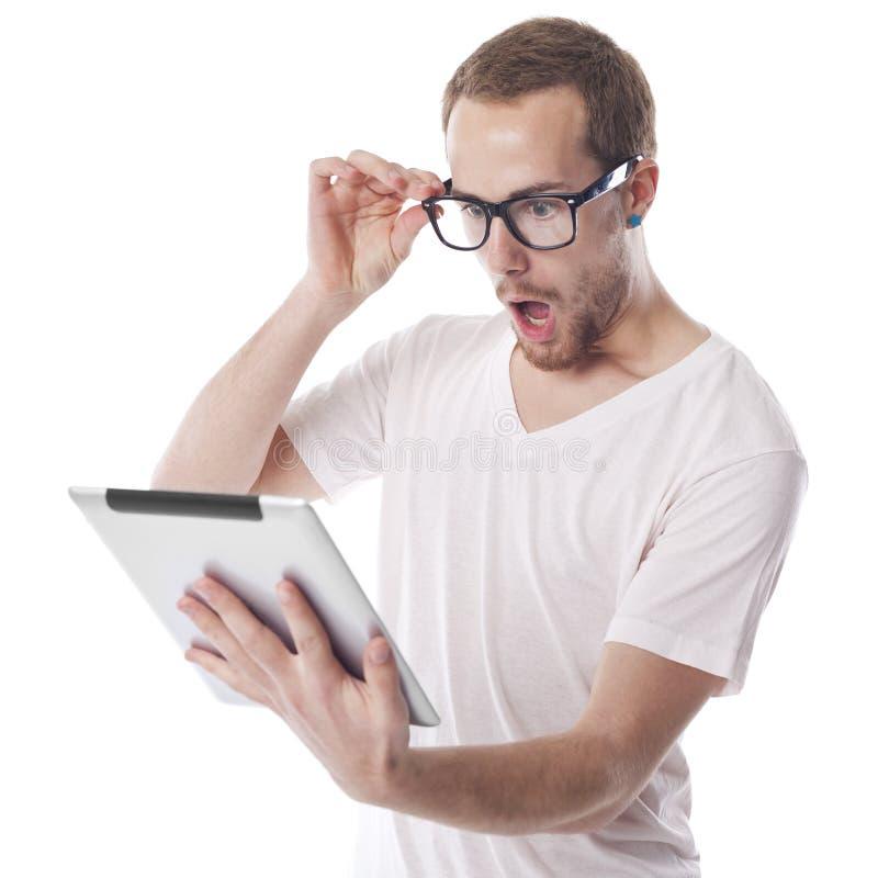 Hombre sorprendido del empollón que mira el ordenador de la tablilla fotografía de archivo