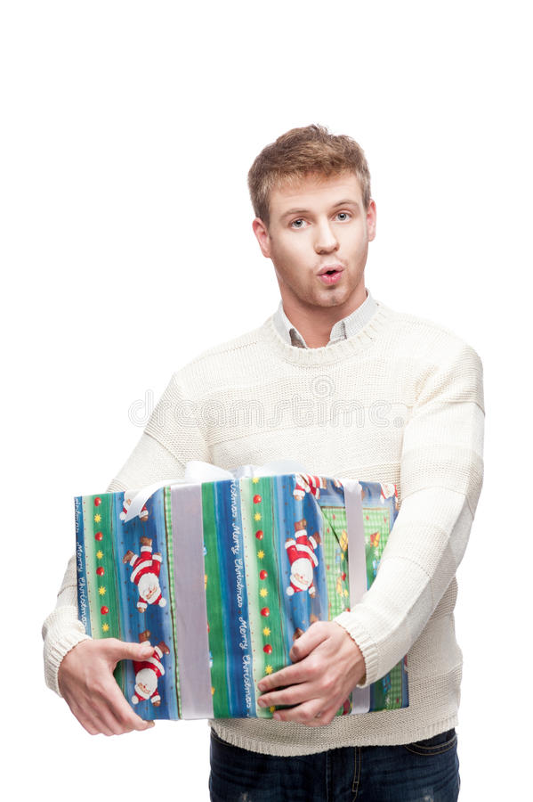 Hombre sorprendido joven que sostiene el regalo pesado grande fotos de archivo libres de regalías
