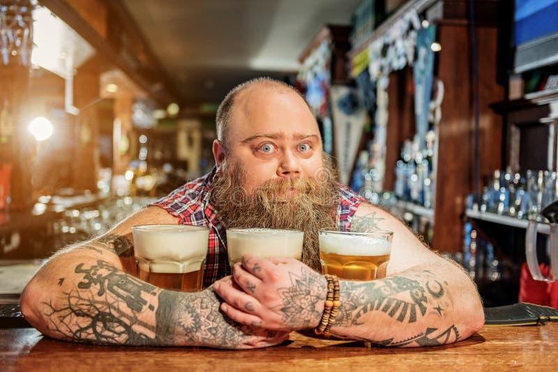Hombre sorprendido que abraza los vidrios de cerveza imagen de archivo